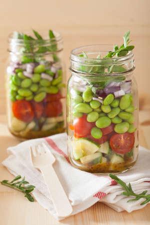 ensalada de verduras: healthy vegetable salad in mason jar: tomato, cucumber, soybean, onion Foto de archivo