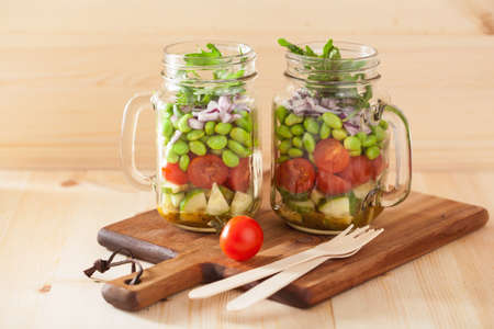 healthy vegetable salad in mason jar: tomato, cucumber, soybean, onion Stock Photo