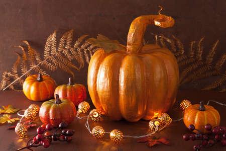 papiermache: decorative golden papier-mache pumpkin and autumn leaves for halloween thanksgiving Stock Photo