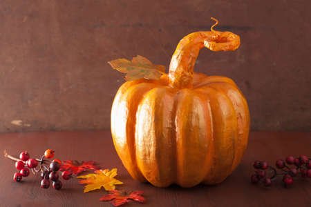 decorative golden papier-mache pumpkin and autumn leaves for halloween thanksgiving Stock Photo