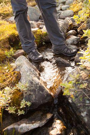 crossing legs: hiker crossing a river. legs in boots
