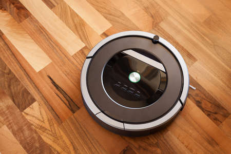 Robotic Vacuum Cleaner On Laminate Wood Floor Smart Cleaning Stock