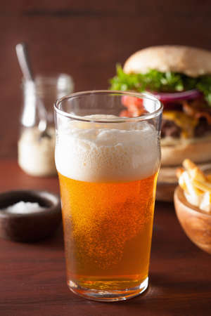 ipa: pint glass of india pale ale beer and fastfood