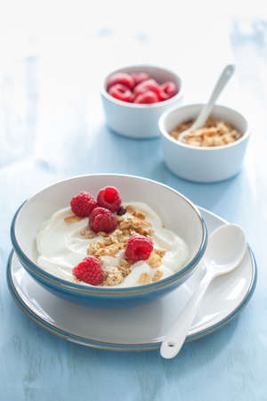 yogurt with granola and raspberry for healthy breakfast Фото со стока