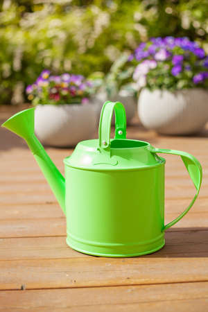 beautyful: watering can and pansy flowers in flowerpots in garden Stock Photo