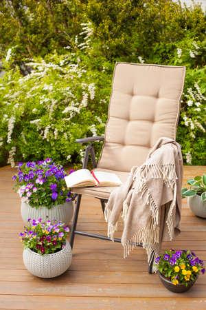 garden chair on terrace in sunlight, flowers  bush Stock Photo