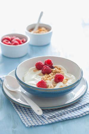 yogurt with granola and raspberry for healthy breakfast Фото со стока