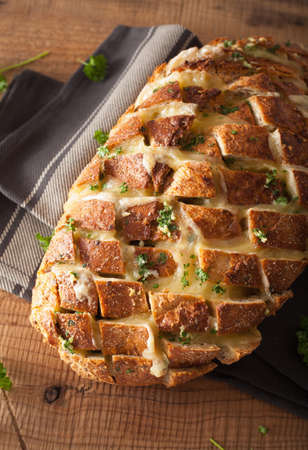 entertaining: baked party bread with melted cheese butter herbs Stock Photo
