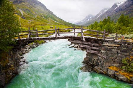 노르웨이의 녹색 강 위에 작은 산책 다리