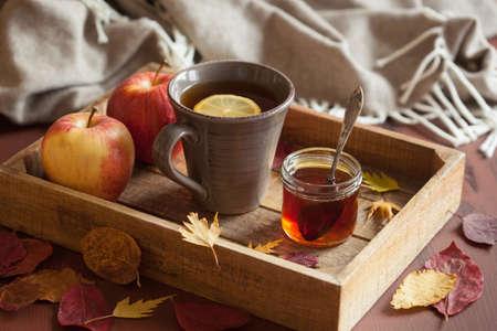 hot lemon honey tea warming drink scarf cozy autumn leaves Stock Photo