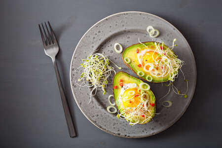 egg baked in avocado with spring onion and alfalfa sprouts