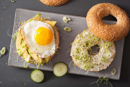 sandwiches on bagels with egg, avocado, soft cheese, alfalfa sprouts Фото со стока