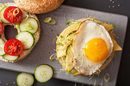sandwiches on bagels with egg, avocado, soft cheese, tomato, cucumber, alfalfa sprouts