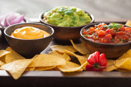 Mexican nachos tortilla chips with guacamole, salsa and cheese dip Stock Photo