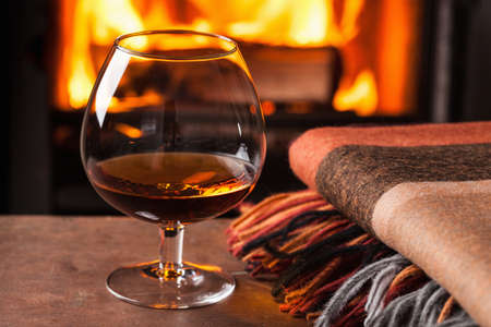 a glass of cognac in front of fireplace