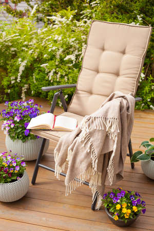 garden chair on terrace and pansy flowers Stock Photo