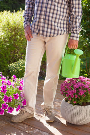 man gardener holding watering can in garden