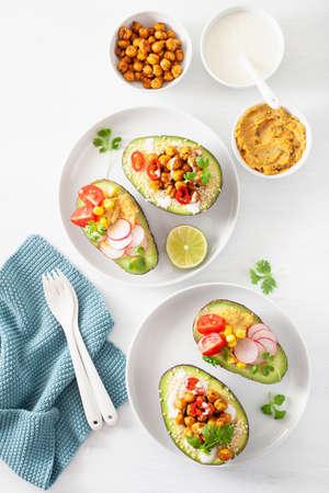 avocado boats stuffed with hummus, tomatoes, radish, roasted chickpea