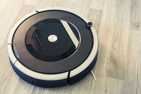 robotic vacuum cleaner on laminate wood floor smart cleaning technology Foto de archivo - 103124404