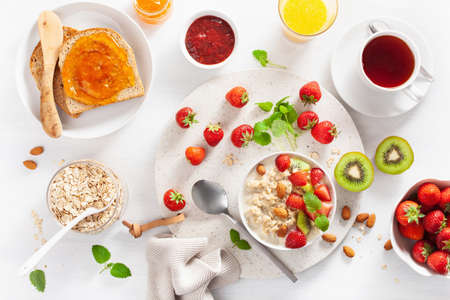 healthy breakfast with oatmeal porridge, strawberry, nuts, toast, jam and tea. Top view Stock fotó - 107292968