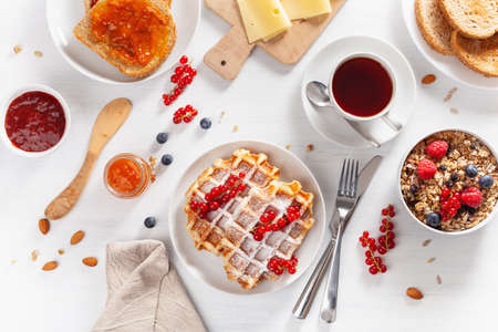 breakfast with granola berry nuts, waffle, toast,  jam and tea. Top view