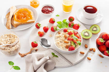 healthy breakfast with oatmeal porridge, strawberry, nuts, toast, jam and tea