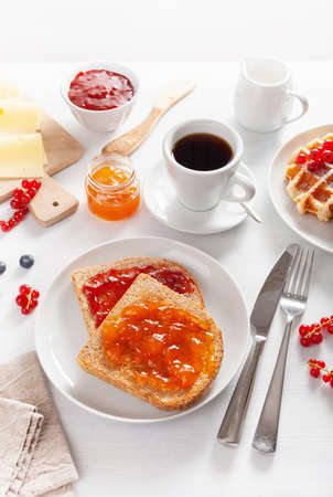 breakfast with waffle, toast, berry, jam, chocolate spread and coffee