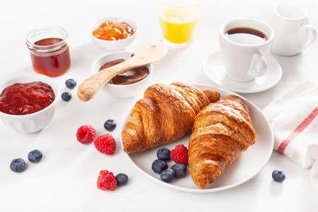 Desayuno continental con croissant, mermelada, chocolate para untar y café.
