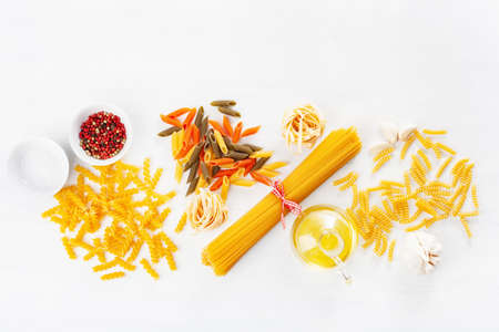 assorted raw pasta flat lay on white. spaghetti fusilli penne tagliatelle girandole