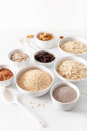 Variedad de cereales crudos y frutos secos para el desayuno. Copos de avena y acero cortado, cebada, nuez, chía, pasas. Ingredientes saludables Foto de archivo