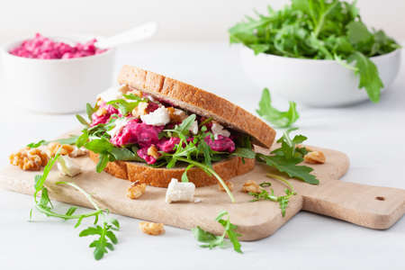 Beetroot and feta cheese sandwich with walnuts and rocket Stock Photo