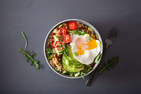 quinoa bowl with fried egg, avocado, tomato, rocket. Healthy vegetarian lunch Stock Photo