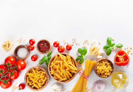ingredients for italian cousine flat lay, pasta, spaghetti, penne, fusilli, tomatoes, oil and vegetables Stock Photo