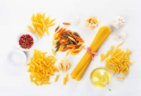 Assorted raw pasta flat lay on white. Spaghetti, fusilli, penne, tagliatelle and girandole