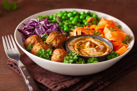healthy vegan lunch bowl with falafel hummus carrot ribbons cabbage and peas Stock Photo