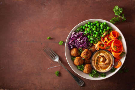healthy vegan lunch bowl with falafel hummus carrot ribbons cabbage and peas Banque d'images