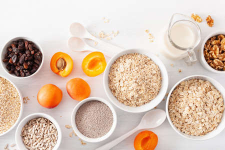 variaty of raw cereals, fruits and nuts for breakfast. Oatmeal flakes and steel cut, barley, walnut, chia, apricot. Healthy ingredients