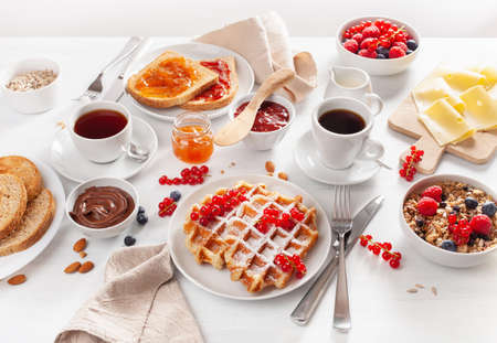 breakfast with granola berry nuts, waffle, toast, jam, chocolate spread and coffee