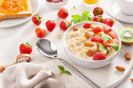 healthy breakfast with oatmeal porridge, strawberry, nuts, toast, jam and tea