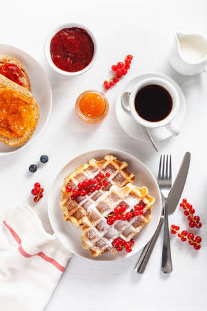 breakfast with waffle, toast, berry, jam, chocolate spread and coffee. Top view