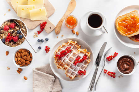 breakfast granola berry nuts, waffle, toast, jam, chocolate spread and coffee. Top view Stockfoto