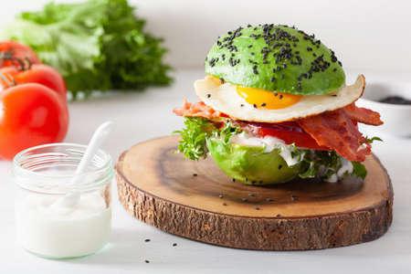 Keto paleo dietetyczny burger śniadaniowy z awokado z bekonem, jajkiem, pomidorem