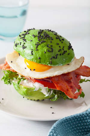 Keto paleo diet avocado breakfast burger with bacon, egg, tomato