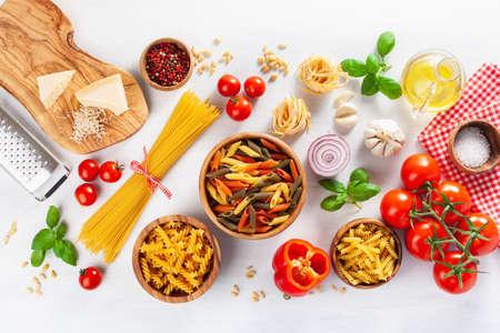 ingredients for italian cousine flat lay, pasta spaghetti penne fusilli tomato oil vegetables