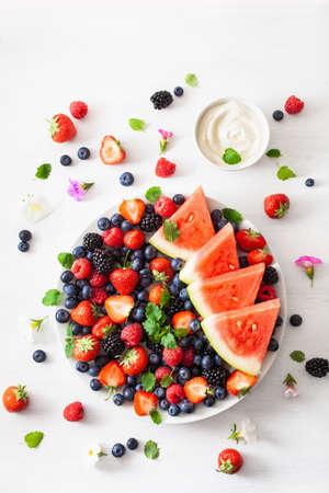 plato de frutas y bayas sobre blanco. arándano, fresa, frambuesa, mora, sandía