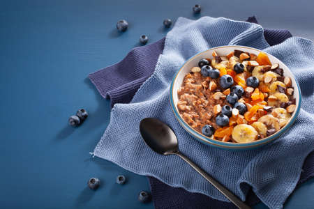 chocolate oatmeal porridge with blueberry, nuts, banana, dried apricot for healthy breakfast