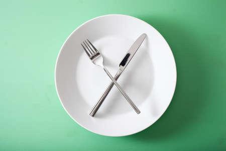 concepto de ayuno intermitente y dieta cetogénica, pérdida de peso. tenedor y cuchillo cruzados en un plato