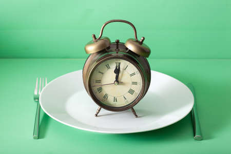 concept of intermittent fasting, ketogenic diet, weight loss. alarm clock on a plate