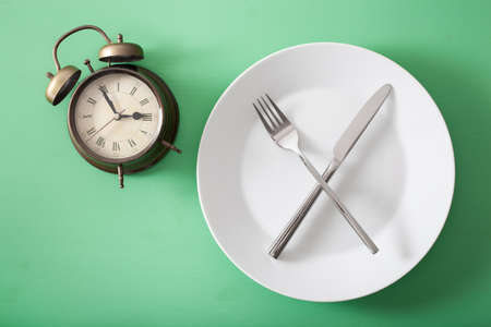 concept of intermittent fasting, ketogenic diet, weight loss. fork and knife crossed on a plate and alarm clock