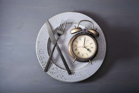 concept of intermittent fasting, ketogenic diet, weight loss. alarm clock fork and knife on a plate Standard-Bild - 127310859